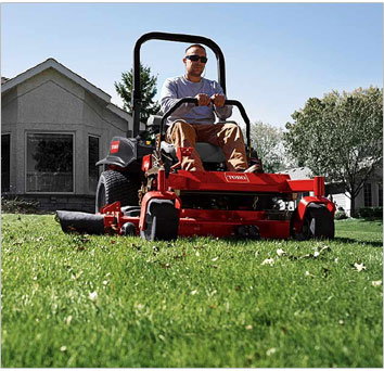 man using lawn mower to landscape backyard